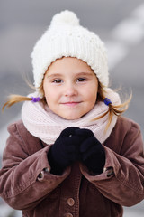 portrait of a child of a little girl in a white warm hat and in a scarf. Warm clothes. Autumn winter. Children's fashion