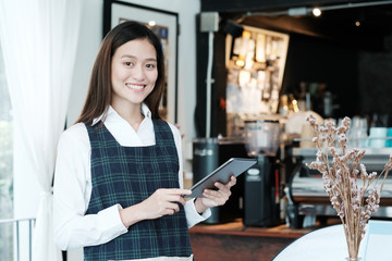 Young asian woman, barista, using tablet to order coffee at cafe counter background, food and drink concept