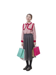 Full body portrait of happy young Asian woman holding shopping bags on white background