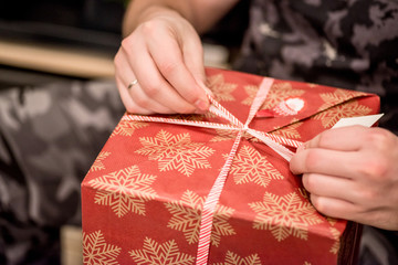 hands wrapping a christmas gift