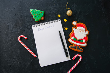 Festive Christmas background, white page of notepad with inscription, candy canes, Santa, stars on a black stone background. Top view with copy space.