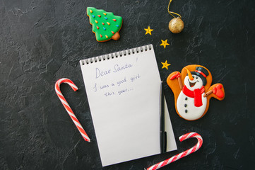 Festive Christmas background, white page of notepad with inscription, candy canes, snowman, stars on a black stone background. Top view with copy space.