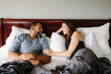 Loving couple talking in bed