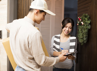 young woman receiving package from delivery man.
