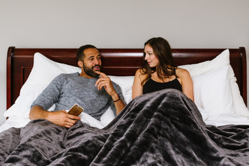 Black and white couple in bed talking