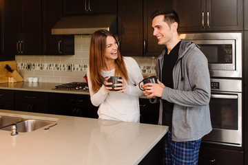 Young happy couple laughing in the kitchen and drinking coffee