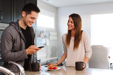 Happy couple in kitchen talking and checking cell phone