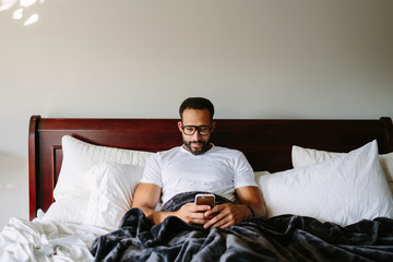 Black man working from bed on his phone