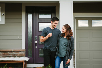 Young couple holding keys in front of new home
