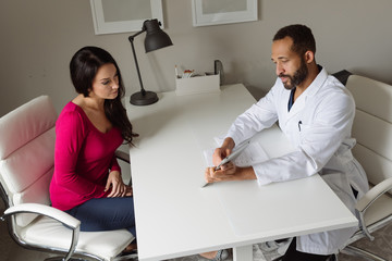 Black doctor meeting with female patient in office