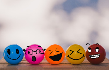 Happy Cheerful Smiley face yellow, orange, red, blue and pink balls with bokeh wall background and copy space