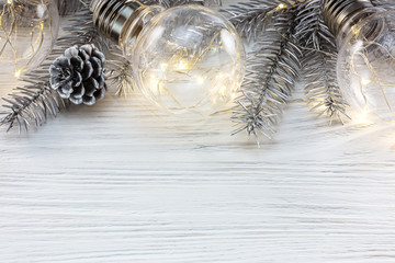 glowing decorative lamp bulbs and silver christmas tree branch on white wooden background