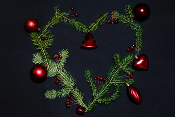 Christmas tree heart with red xmas toys and balls on a dark background