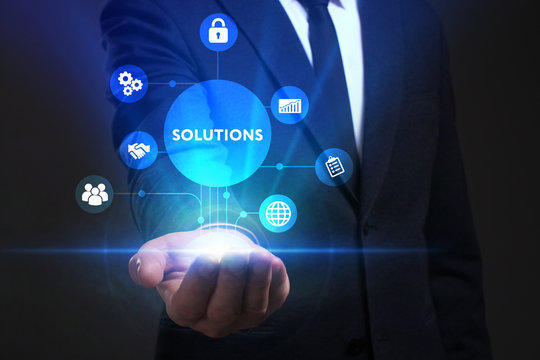 Business, Technology, Internet and network concept. Young businessman working on a virtual screen of the future and sees the inscription: Solutions
