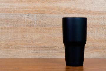Black colour stainless steel tumbler or cold storage cup on wood background.