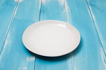 White Round plate on blue wooden table with perspective