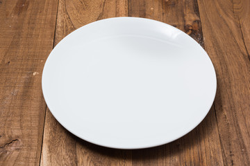 White Plate on brown wooden background side view