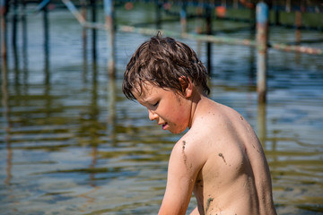 Boy playing with water and dirt in a polish lake, summer holiday in Greater Poland. Leisure, child having fun and joy- boys point of view. Beautiful childhood.