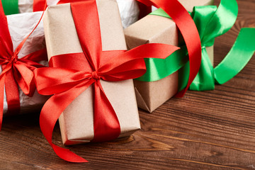 Christmas Gift boxes and decorations. Gift box in kraft paper with a red ribbon on a wooden background. Christmas background.