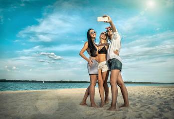 Three young pretty women in sunglasses having fun on the beach a