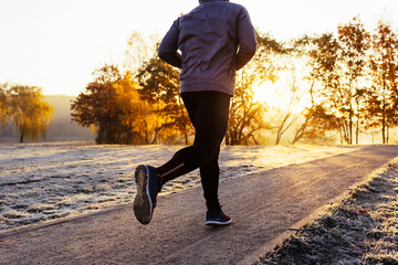 Close-up of man jogging on sunny autumn morning outdoors
