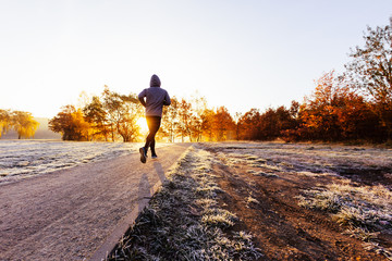 Man jogging outdoors, working out on sunny autumn morning