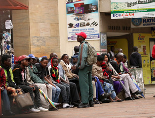 People queue to draw money outside a bank in Harare