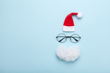 Creative christmas composition. Greeting card, invitation or flyer. Santa hat, beard and glasses on blue background top view. Flat lay.