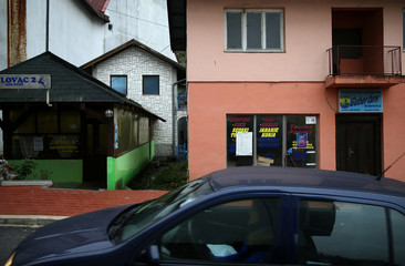 Car passes by closed restaurant and tourist agency in Srebrenica