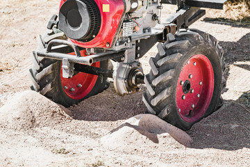 The small handy farm machine motor plow closeup standing in deserted rural landscape in sand