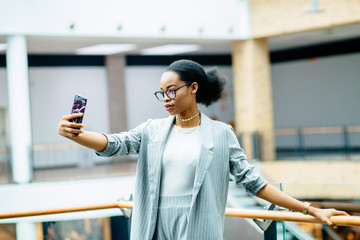 Serious african business student woman doing selfie on smart phone while standing at railing in business center or shopping mall. Lifestyle, leisure and people concept.