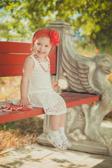 Retro stylish dressed blond young baby girl child posing in central park garden wearing french couturer white dress red bandana and chaplet