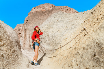 Asian female traveler in the Middle Eastern desert in national dress with a turban, climbing up the stairs