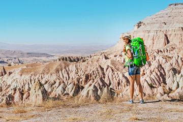 Young happy active tourist woman with backpack travel and trekking at Cappadocian deserted canyons and valleys, Turkey.