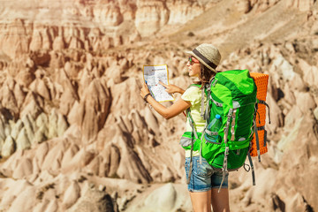 Active young tourist backpacker travels among cappadocia sandstone canyons and cave towns at summer and reading map