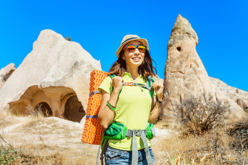 Young happy woman traveler alone hiking with backpack in the cave city in rose valley of Cappadocia, Turkey