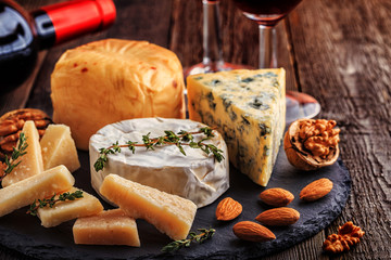 Cheese, nuts, honey and red wine on wooden background.