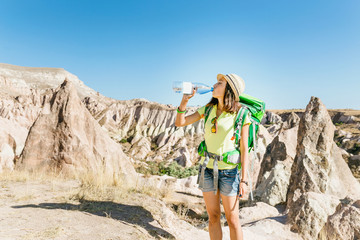 A tired woman during a track on a mountain desert landscape drinks from a bottle of clean water