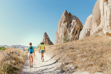 Group of Friends travelling among Cappadocia fairy chimneys at summer