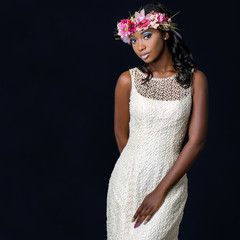 Close up studio portrait of attractive young african bride wearing white wedding gown. Medium shot of girl with colorful flower garland against dark background.