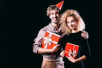 Happy couple hold red presents box, man and woman smile looking at camera embracing.