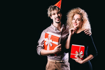Happy couple with red gift boxes, man and woman smile looking at camera embracing, isolated on black.