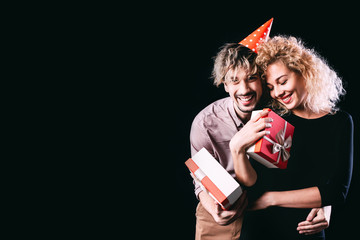 Loving couple. Beautiful man and woman holding gift boxes on a dark background.