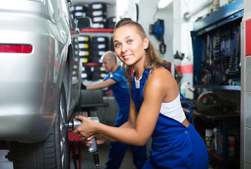 woman technician fitting new tires to car at workshop