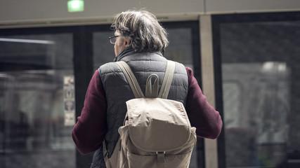 Senior man passenger in public train station in city