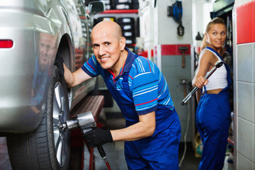 Mature male technician fitting new car tyre