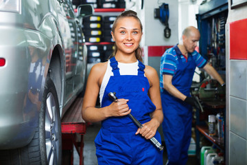 Woman in work coveralls working in auto service point