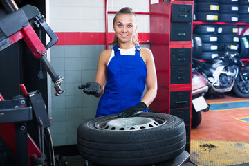 Woman technician standing with wheel