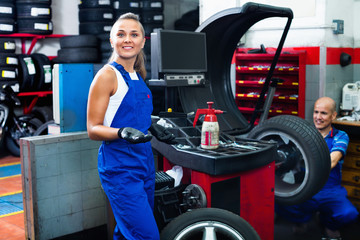Mechanic woman working on new tire fitting in service point