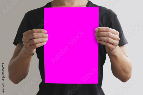 Man in black t shirt holding blank pink A4 paper vertically. Leaflet  presentation. Pamphlet